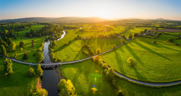 Aerial panorama over idyllic countryside green fields mountains golden sunset stock photo