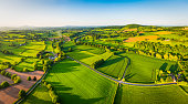Aerial panorama over picturesque river valley meandering between rolling hills of patchwork pasture, agricultural crops, rural homes and green summer landscape.