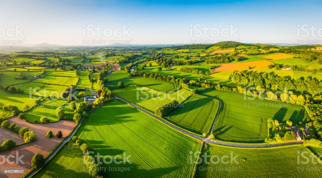Aerial panorama over idyllic green summer farm fields crops pasture stock photo