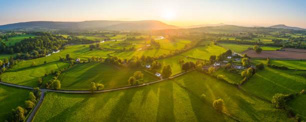 Aerial panorama over idyllic rural landscape farms fields golden sunlight stock photo