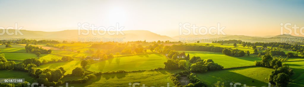 Aerial panorama over idyllic rural landscape golden sunset green pasture stock photo