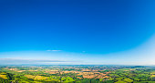 Big blue summer skies over picturesque patchwork landscape of green pasture and golden crop fields, rural villages, farms and country towns. ProPhoto RGB profile for maximum color fidelity and gamut.