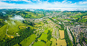 Big blue summer skies and white fluffy clouds above country villages, rolling hills, green fields and the picturesque patchwork pasture of this rural panorama from high above.