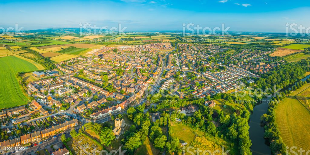 Aerial panorama over town river suburban homes surrounded by fields stock photo