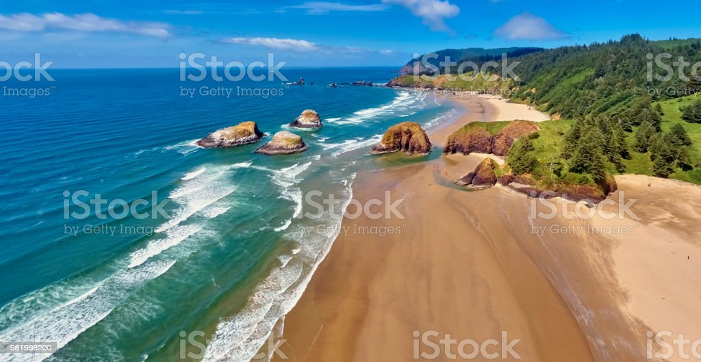 Aerial panorama shot at approximately 350 feet above Cannon Beach looking towards Ecola State Park on a sunny blue sky day on the Oregon Coast stock photo