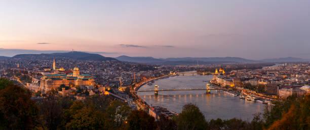 夕暮れ時のピンクの空と秋の季節に照らさブダペストの空中パノラマの街並み - マーチャーシュ教会 ストックフォトと画像