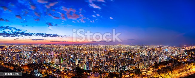 Colored Aerial Panoramic View of Belo Horizonte Cityscape, Minas Gerais State, Brazil. Image taken from Water Tank Viewpoint during Sunset with a Multicolored Sky and Buildings with some Lights already on.