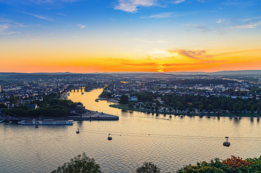 Aerial panoramic view of Koblenz historical city centre and joining Rhine and Moselle rivers, evening twilight view of amazing colorful orange sunset on horizon, Rhineland-Palatinate state