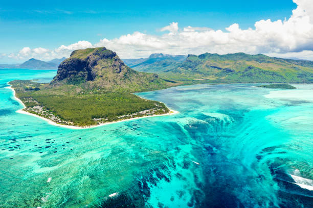 Aerial panoramic view of Mauritius island - Detail of Le Morne Brabant mountain with underwater waterfall perspective optic illusion - Wanderlust and travel concept with nature wonders on vivid filter stock photo