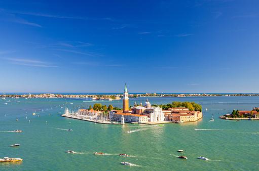Aerial panoramic view of San Giorgio Maggiore island with Campanile San Giorgio in Venetian Lagoon, sailing boats in Giudecca Canal, Lido island, blue sky background, Venice city, Veneto Region, Italy