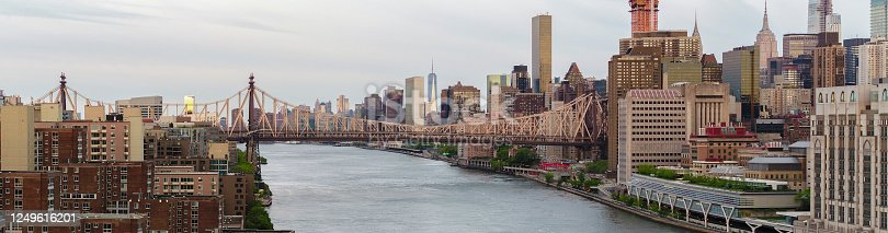 istock Aerial panoramic view of the Ed Koch Queensboro Bridge connecting Queens and Manhattan over the Roosevelt Island on East River, with the remote view of Downtown  Manhattan and Freedom Tower in the backdrop, in the early morning. New York, USA. 1249616201