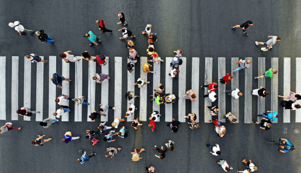 aerial. people crowd motion through the pedestrian crosswalk. top view from drone. - folla foto e immagini stock