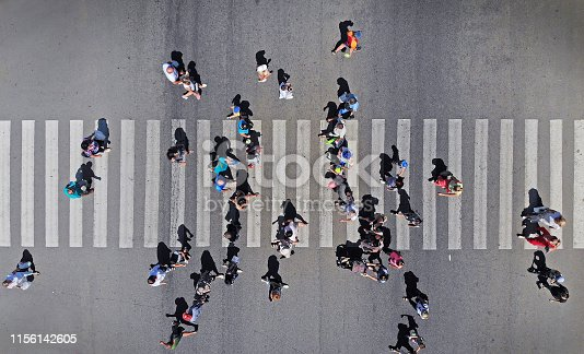 Aerial. People crowd on pedestrian crosswalk. Top view.