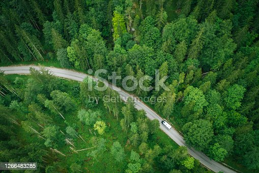 istock Aerial perspective of a motor home driving down a road through the forest 1266483285