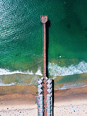 Aerial photo of a very long pier with houses and cars in San Diego California