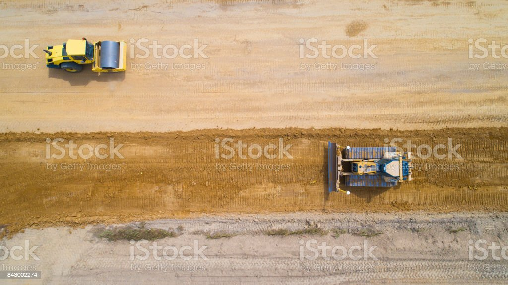 An aerial view on a yellow steam roller and a backhoe working on a...