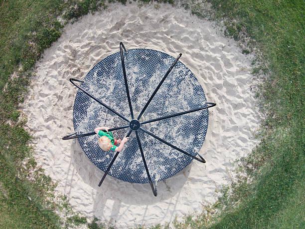 aérienne de la photo d'un jeune garçon jouant sur un rond-point - rond point photos et images de collection