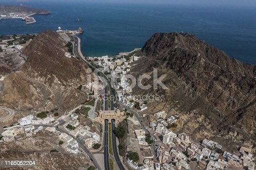 Two lanes of Al Bahri road passing below the Muscat Gate in Old Muscat, Oman.