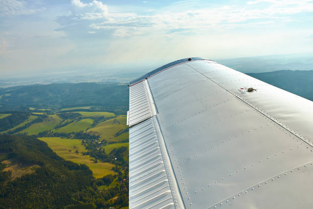 Aerial photo of landscape with fields, meadows and forests with a small airplane wing in foreground stock photo