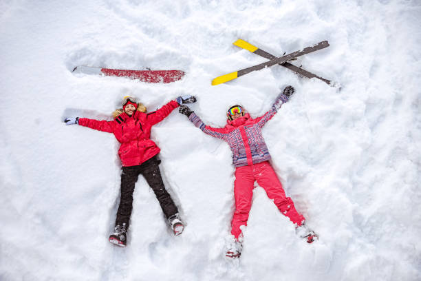 Aerial photo of skier and snowboarder lying on snow