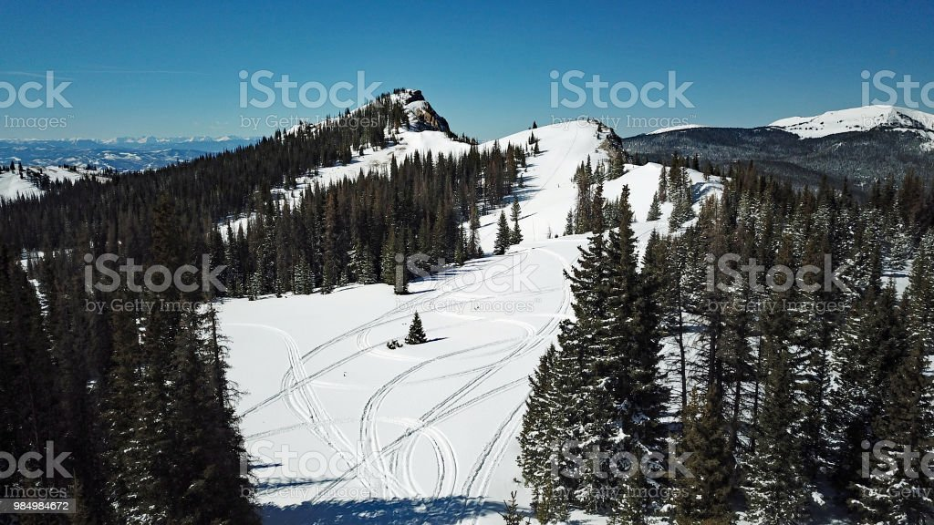 Aerial Photo Of Snowmobile Tracks In The Mountain Snow Stock Photo