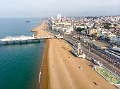 istock Aerial photo of the famous Brighton Pier and ocean located in the south coast of England UK that is part of the City of Brighton and Hove, taken on a bright sunny day showing the fairground rides. 1171580495