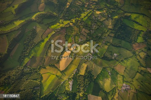 Vibrant green crops, ploughed fields and pasture, hedgerows and woodland surrounding farms and villages in an idyllic rural patchwork quilt landscape from high above. ProPhoto RGB profile for maximum color fidelity and gamut.
