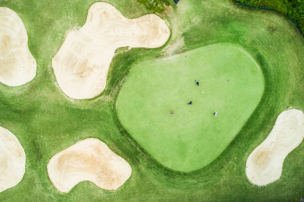 Aerial photograph of a golf course on a sunny day. There is no one wide golf course. green golf course stock pictures, royalty-free photos & images