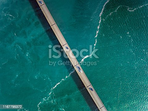 Sea surrounding a bridge and cars driving across the bridge to reach their destination.