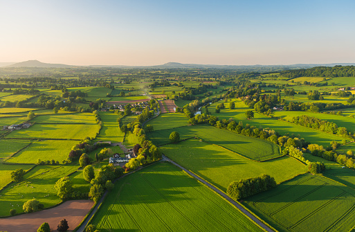 Warm sunset light illuminating the picturesque patchwork quilt landscape of green pasture, agricultural crops, farms and villages below clear blue panoramic skies.
