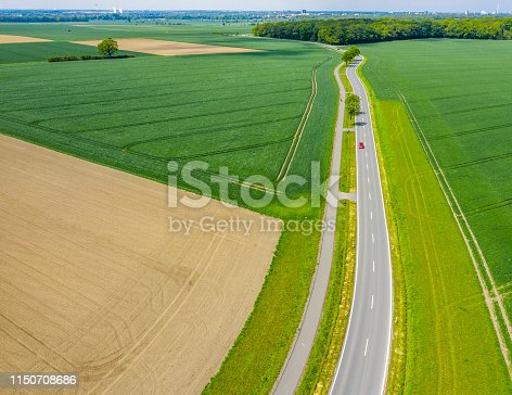 1095367134 istock photo Aerial photograph with the drone camera of a small asphalted country road leading through fields and meadows, drone shot 1150708686