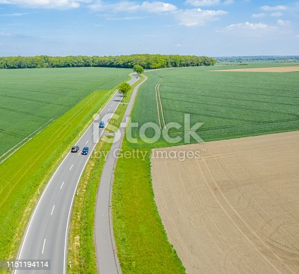 1095367134 istock photo Aerial photograph with the drone camera of a small asphalted country road leading through fields and meadows, drone shot 1151194114