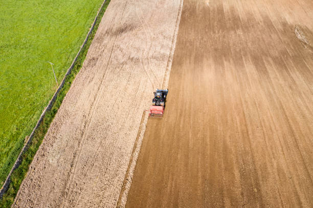 Aerial rear view of a tractor being used to pull a seed drill on a Scottish farm on a late summer day The view from a drone of a tractor pulling a seed drill which is sowing wheat to be harvested next year. The location is a rural area of Dumfries and Galloway in south west Scotland. johnfscott stock pictures, royalty-free photos & images