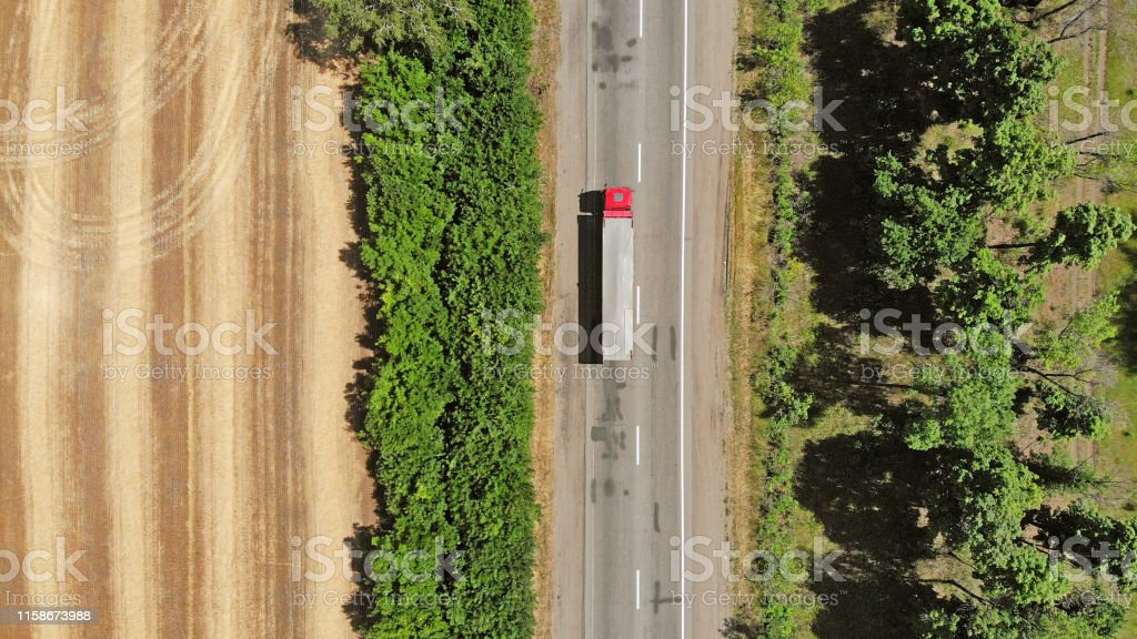Aerial. Red truck on a road between fields. Transport logistics...