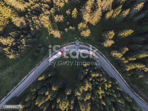 Drone point of view over a road curve in the pine woodland in the Rodopi mountains. Drone's flight directly above over a big motorway during the COVID-19 pandemic. Transportation event.