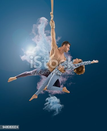 istock Aerial rope artist couple performing in the air at circus 948083024