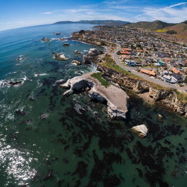 Luftbildende Ansicht des Pismo Beach, der kleinen Stadt am Pazifischen Ozean, der kalifornischen Westküste, am sonnigen Frühlingstag. Die Klippe mit Grotten bedeckt sind Seevögel Nester. Treibkraut im transparenten klaren Wasser schwimmen. Hochauflösen – Foto