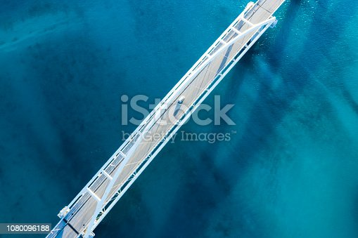 Clear ocean. Viewpoint from directly above. The shadow of the bridge appears on the surface of the water.