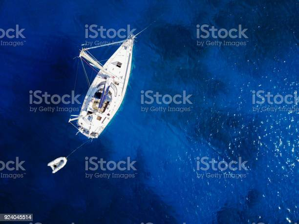 Photo of Aerial shot of beautiful blue lagoon at hot summer day. Top view of sailing boat ready for cruise.