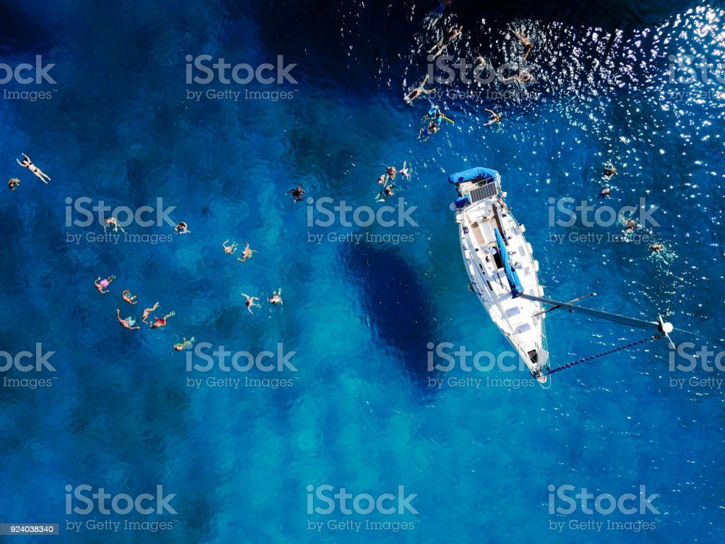 Aerial shot of beautiful blue lagoon at hot summer day with sail stock photo
