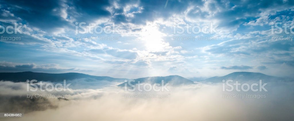 Aerial shot of mountain village under clouds stock photo