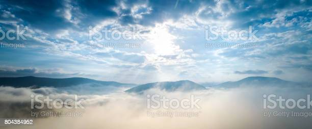 Photo of Aerial shot of mountain village under clouds