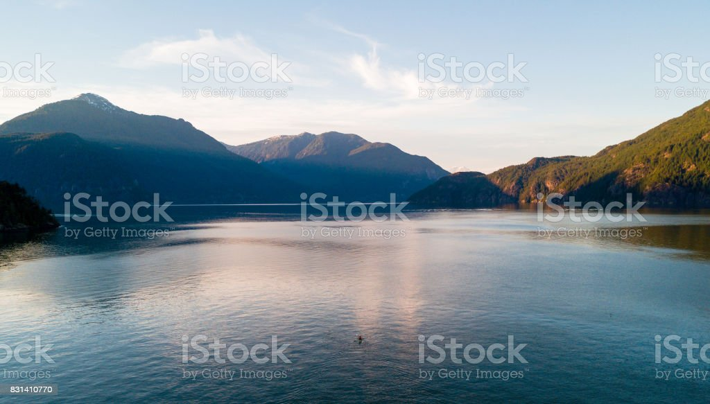 Aerial shot of ocean bay or lake with mountains while  sunset stock photo