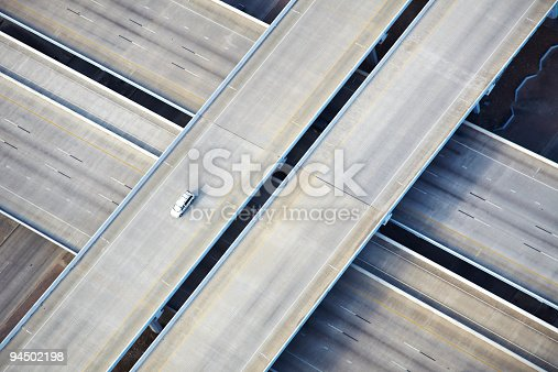 94502198 istock photo Aerial shot of one car on freeway 94502198