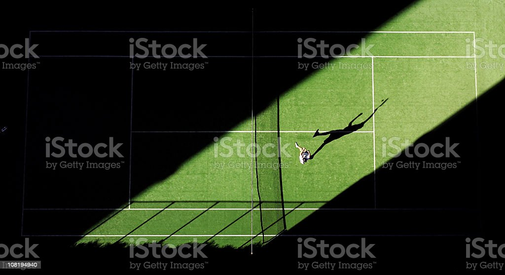Aerial shot of tennis match from above with player's shadow stock photo
