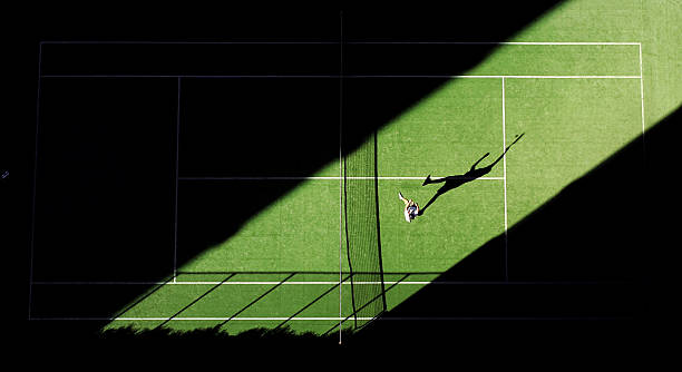 aerial shot of tennis match from above with player's shadow - tennis stock pictures, royalty-free photos & images