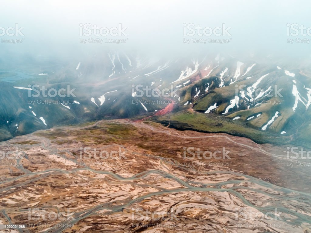 Aerial view of volcanic landscape in foggy weather. Drone shot of...