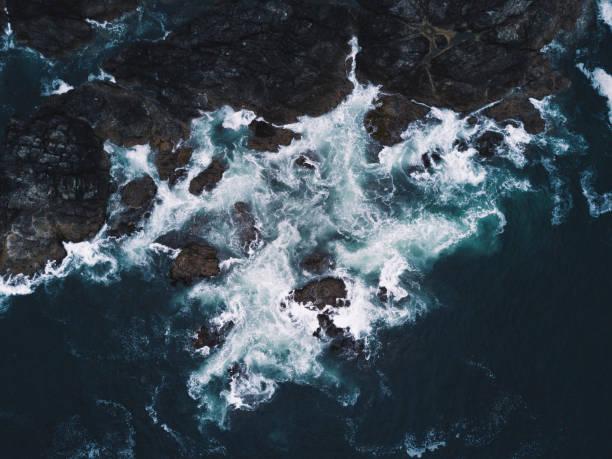 Aerial shot of waves hitting rocks on ocean coast stock photo