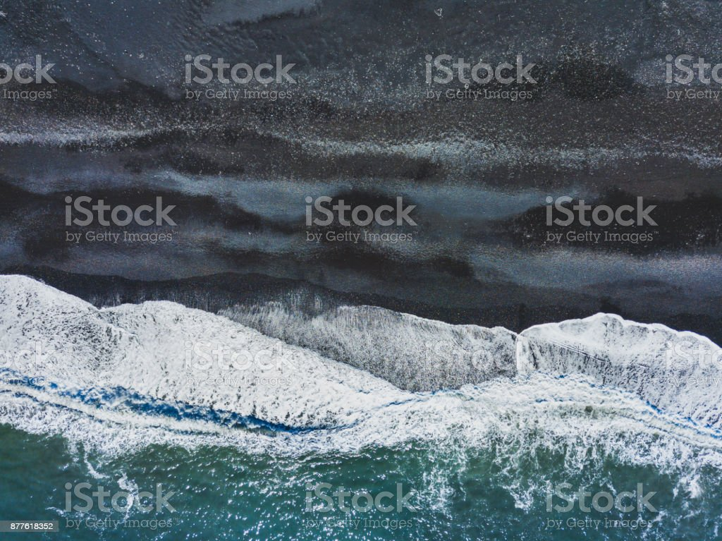 aerial shot of waves on black sand beach stock photo
