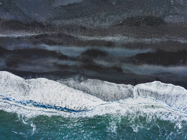 aerial shot of waves on black sand beach aerial shot of waves on black sand beach in Iceland, top view landscape from drone black sand stock pictures, royalty-free photos & images